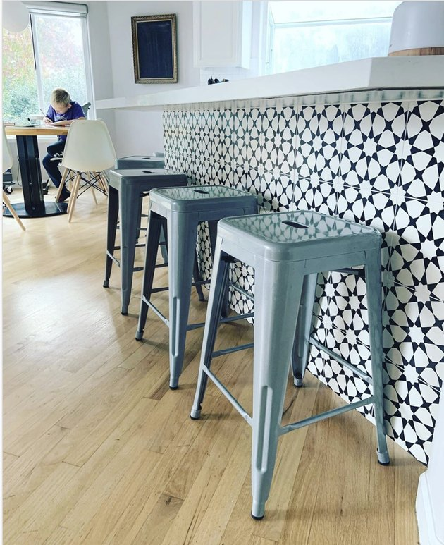 black and white tile on kitchen island table with blue barstools