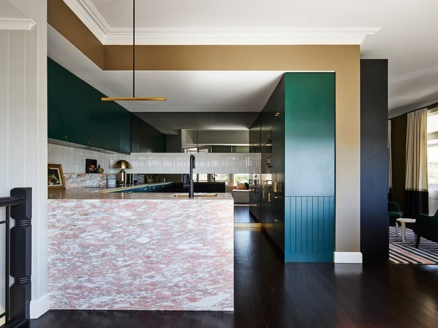 Art deco kitchen with pink stone island and green cabinets
