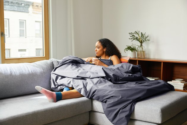 woman on sofa wrapped in weighted comforter