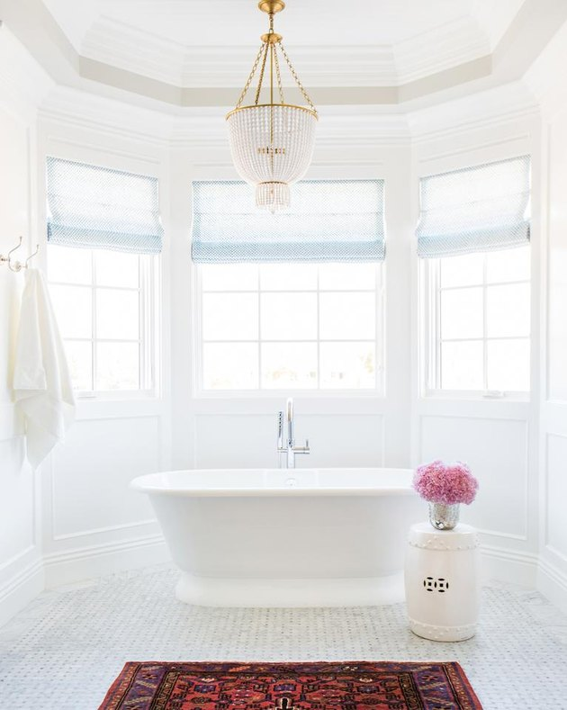 bathroom chandelier lighting idea with crystal and brass fixture hanging over tub
