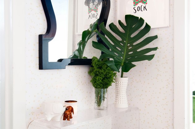 Minimalist entryway design with decorative mirror above clear console table with plant leaves in vases.