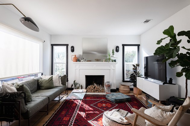 Bright family room with fireplace and TV layout paired with gray couch and fig tree.