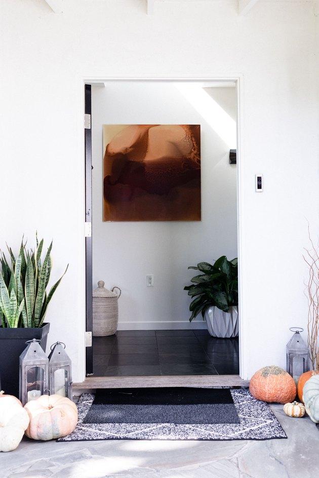 Minimalist entryway design with plants, artwork, pumpkins, lanterns, and art