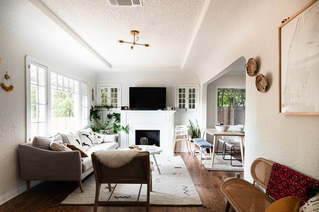 Family room with fireplace and TV layout and large windows.