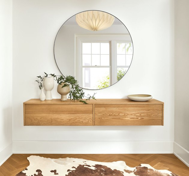 Minimalist entryway design with circular mirror over floating wood cabinet on white wall with cowhide below.