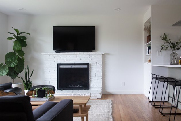White walled family room with fireplace and TV layout and fig tree