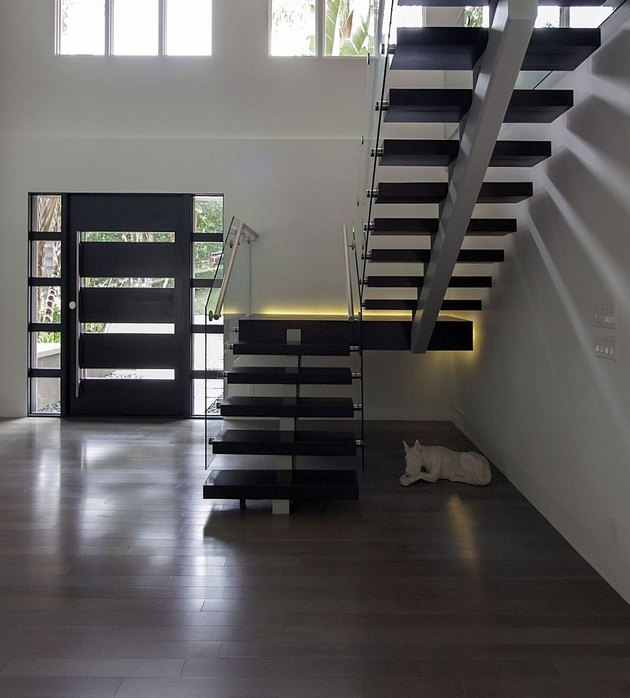 Minimalist entryway design with custom modern dark wood door and floating staircase