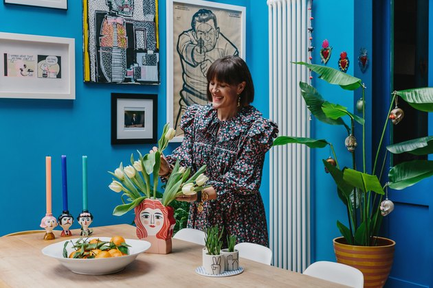 Zoe Anderson arranging tulips in her bright blue dining room