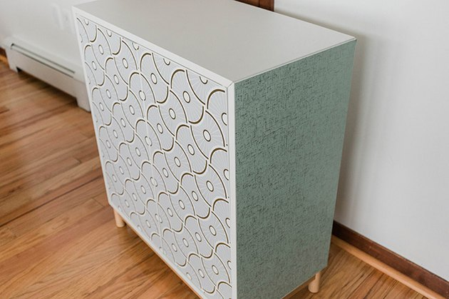 Attach the wallpaper pieces to the front and sides of the cabinet.