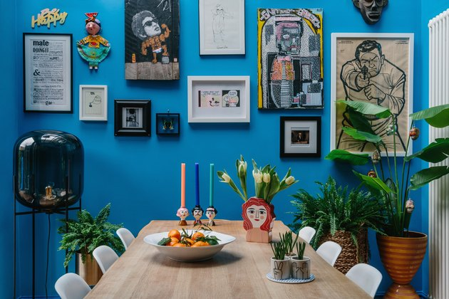 bright blue dining room with gallery wall