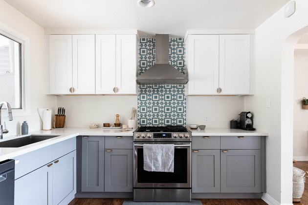 kitchen with grey and white kitchen cabinets, stove, exposed ventilation and mosiac tile backsplash
