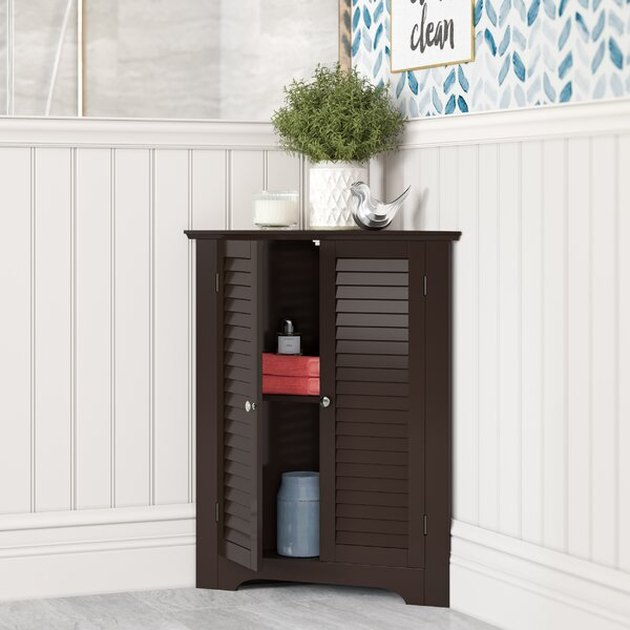 Multipurpose Corner Bathroom Cabinet with Shutter Doors and potted plant on top