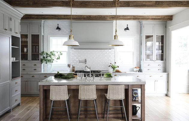 concrete and wood rustic kitchen island in kitchen with white tile backsplash
