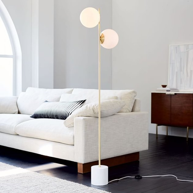 living room space with white couch and floor lamp