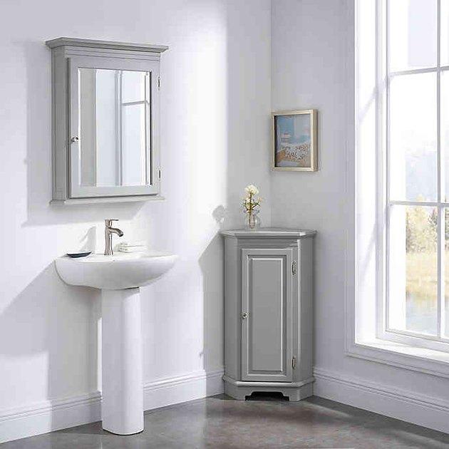Gray corner bathroom cabinet with floating medicine cabinet and pedestal sink