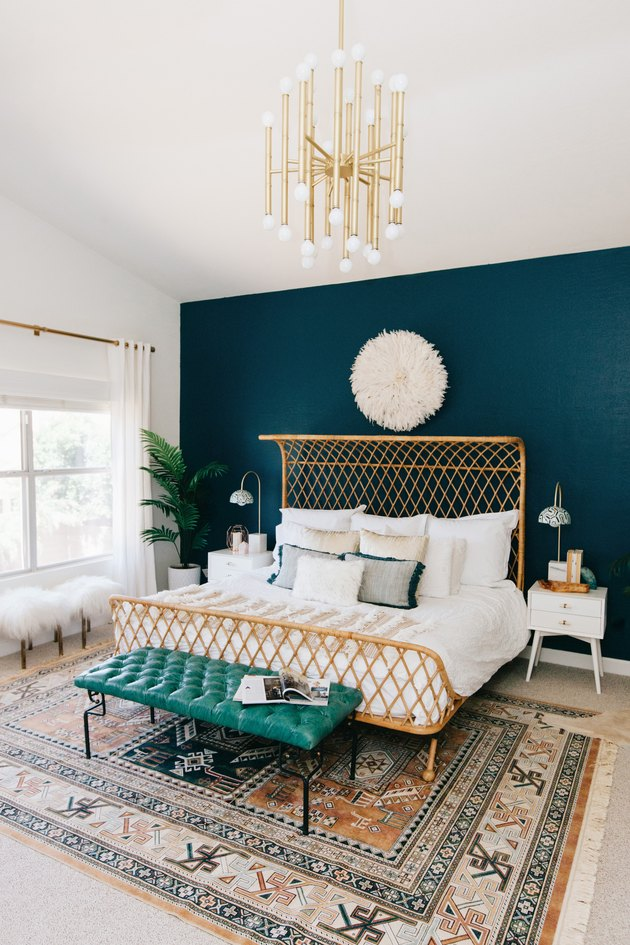 blue bohemian bedroom with rattan bed and midcentury light fixtture