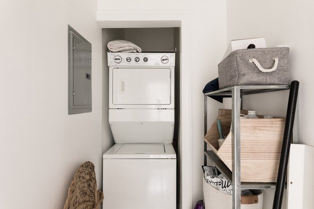 laundry room featuring standing washer-dryer with laundry baskets and breaker box