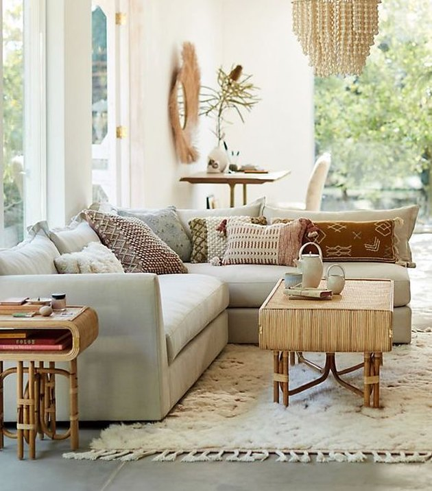 living room rug idea with an off-white flokati rug, a bamboo coffee table, and a stuffed, light-color sectoinal
