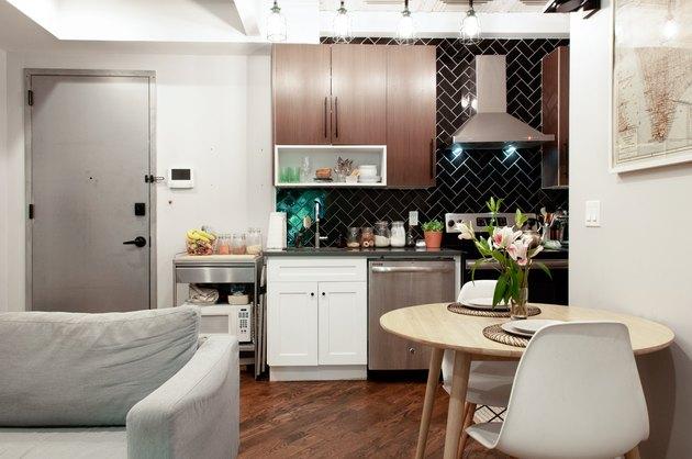 small kitchen with dark chevron tile backsplash, dark wood cabinets, stove and vented range hood