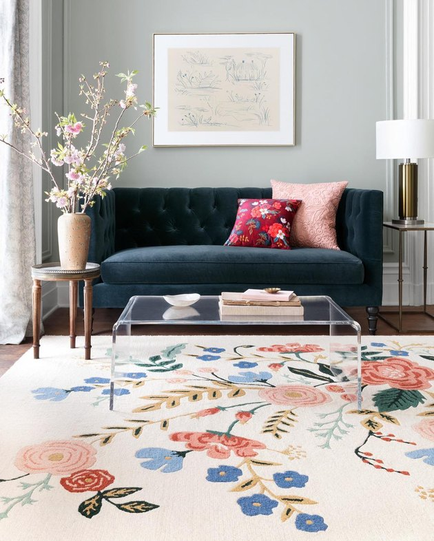 living room rug idea with a light pink rug with a large floral design, an acrylic coffee table sits on top and a dark velvet couch is in the background