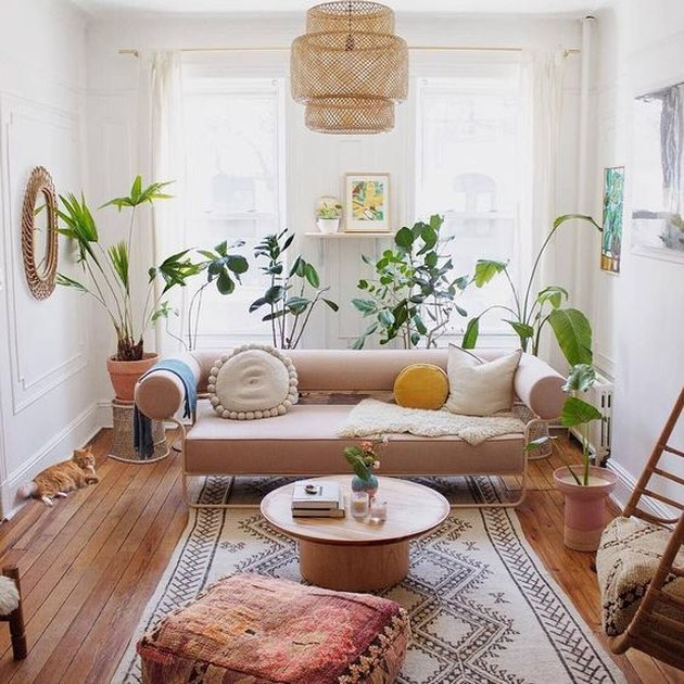 living room rug idea with airy, narrow living room with a light pink couch, round coffee table and kilim pouf on a black and cream rectangular rug