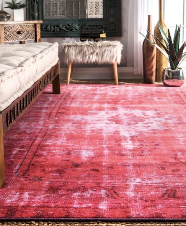 living room rug idea with a bright pink rug under a wood-framed couch, with a faux-fur ottoman in the background