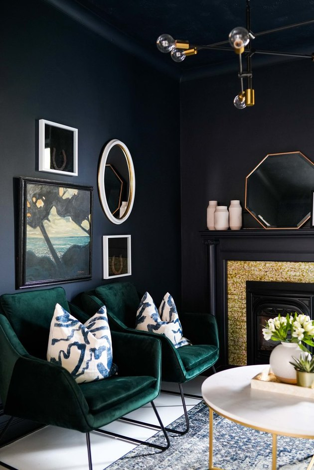 black walls in living space with green velvet chairs