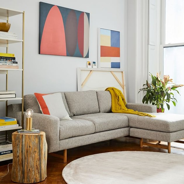 living room rug idea with a round light gray rug in front of a tan sectional, with abstract art behind it on the wall