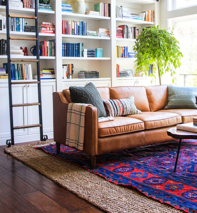 living room rug idea with leather couch in a home library, placed on a bright blue and red vintage rug, layered over a jute area rug