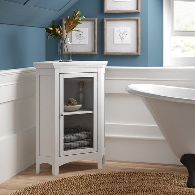 Low white corner bathroom cabinet with clawfoot bathtub and blue–painted walls