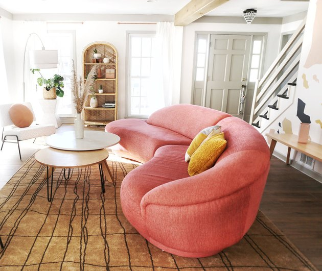 art deco living room with pink curved sofa and rattan bookshelves