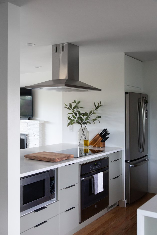kitchen with induction stovetop, white countertops, and vent hood attached to ceiling