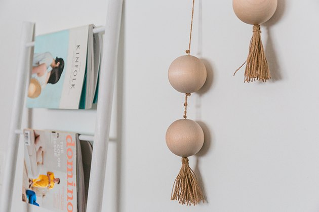 Hang the finished threaded beads on the wall using a hammer and picture hanging nails.
