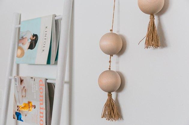 Accrochez les perles filetées finies sur le mur à l'aide d'un marteau et de clous suspendus.