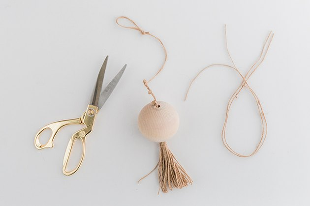 Tie a few decorative knots along the length of the twine, then knot a loop into the end.