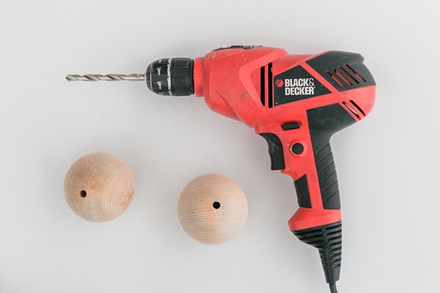 Drill holes through the wood balls.