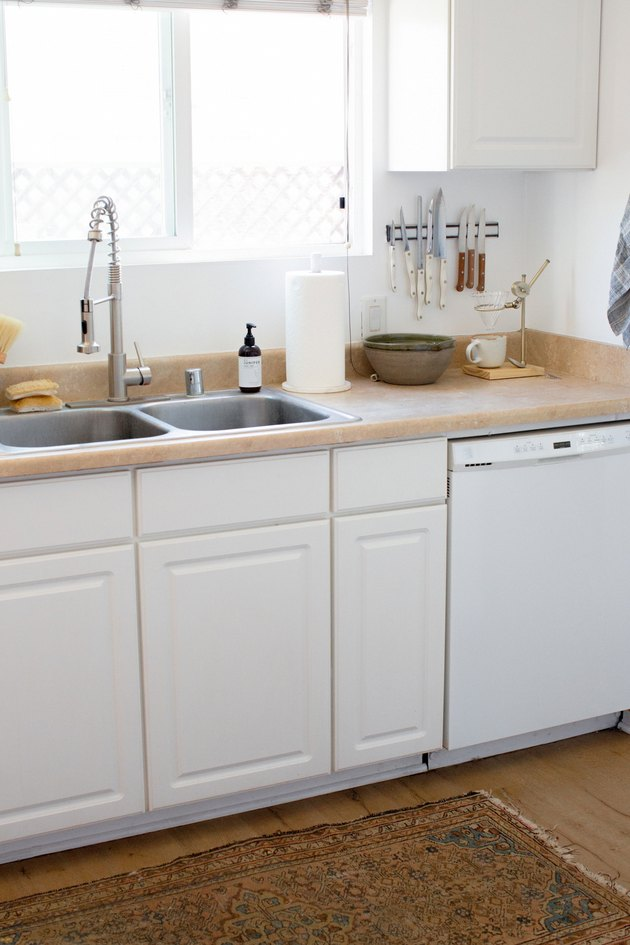 white kitchen cabinetry, wood countertops and pull down kitchen sink faucet