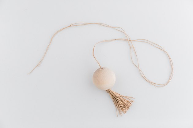 Thread the long twine end through the wood ball and pull it through until the tassel hits the bottom of the ball.
