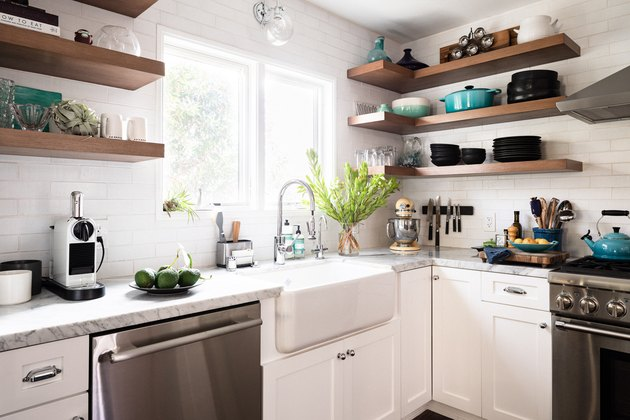 kitchen with white cabinetry, farmhouse sink, stainless steel appliances and wooden shelving units above