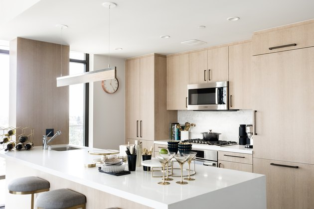 kitchen with light wood cabinetry, white countertops, stovetop and microwave