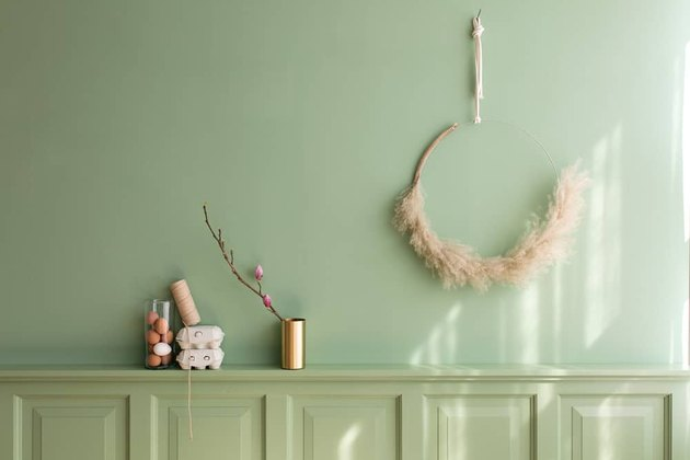 DIY minimalist wreath with pampas grass on brass ring hanging on green wall above matching buffet