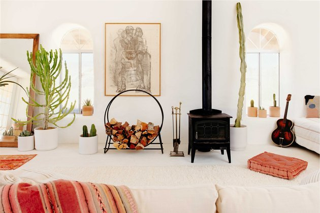 desert living room with wood burning stove and potted cacti, floor pillow seating