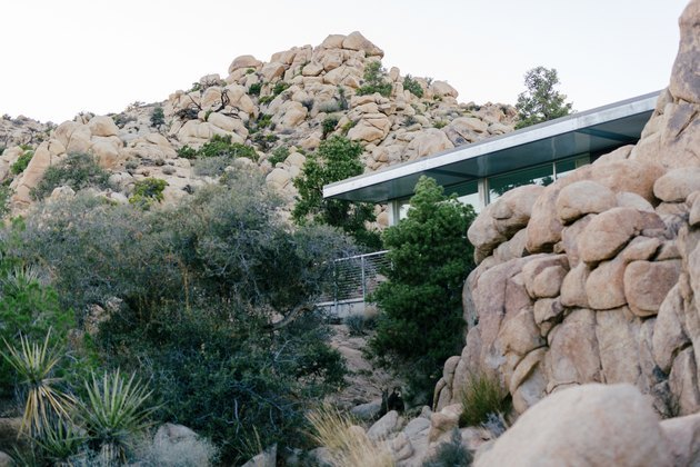 modern midcentury-style prefab house set within large desert boulders