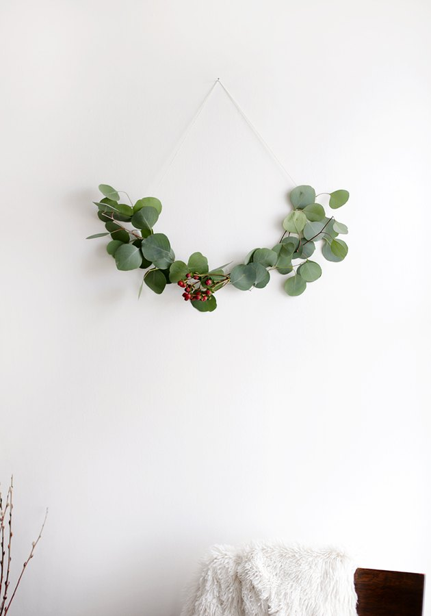 DIY minimalist wreath with greenery on white wall