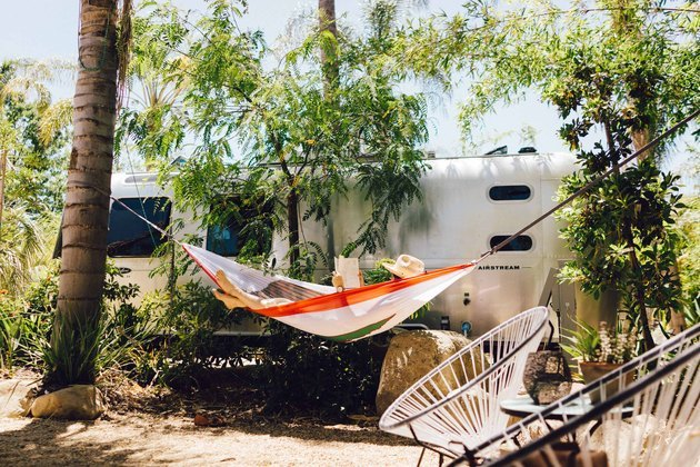 vintage Airstream with person reading in hammock and boho modern outdoor seating