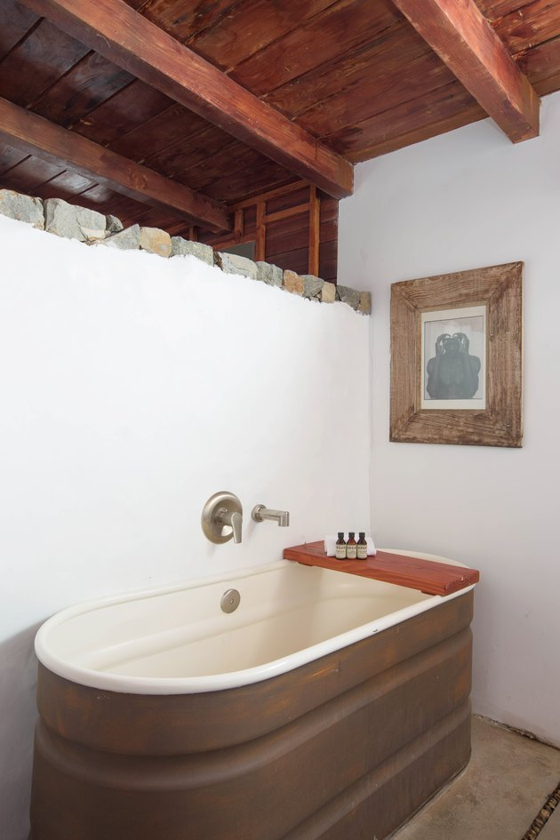 redwood open beamed ceiling in bathroom with horse trough bathtub and redwood bath caddy