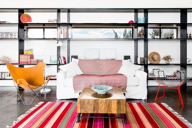 modern industrial home with bright pops of colorful furniture and contrasting bookcase