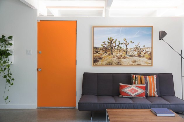 modern entryway living room with bright orange front door and midcentury style furniture
