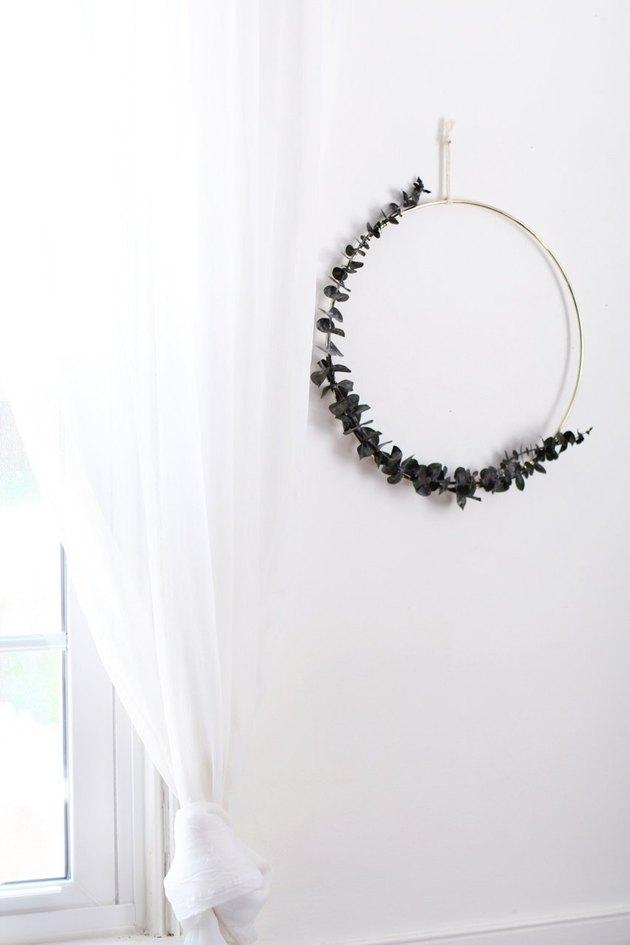 DIY minimalist wreath with eucalyptus in white room next to window