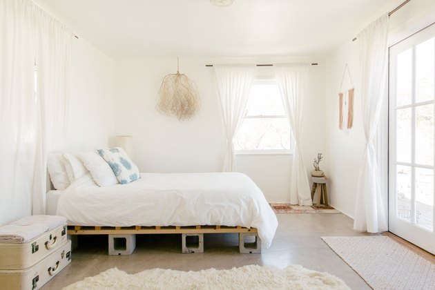 airy all-white bedroom with tumbleweed wall hanging and French doors